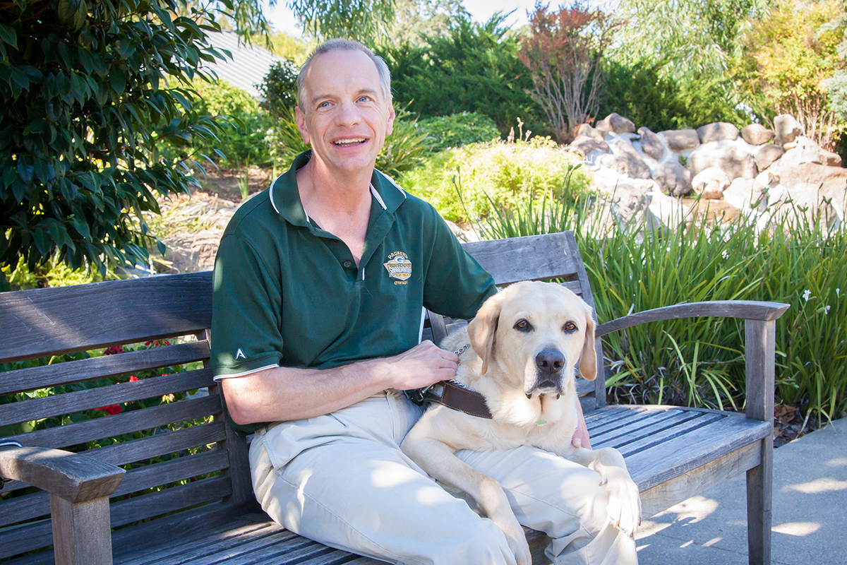 A portrait of Jack Heim sitting next to a yellow Lab guide dog, Guillermo.