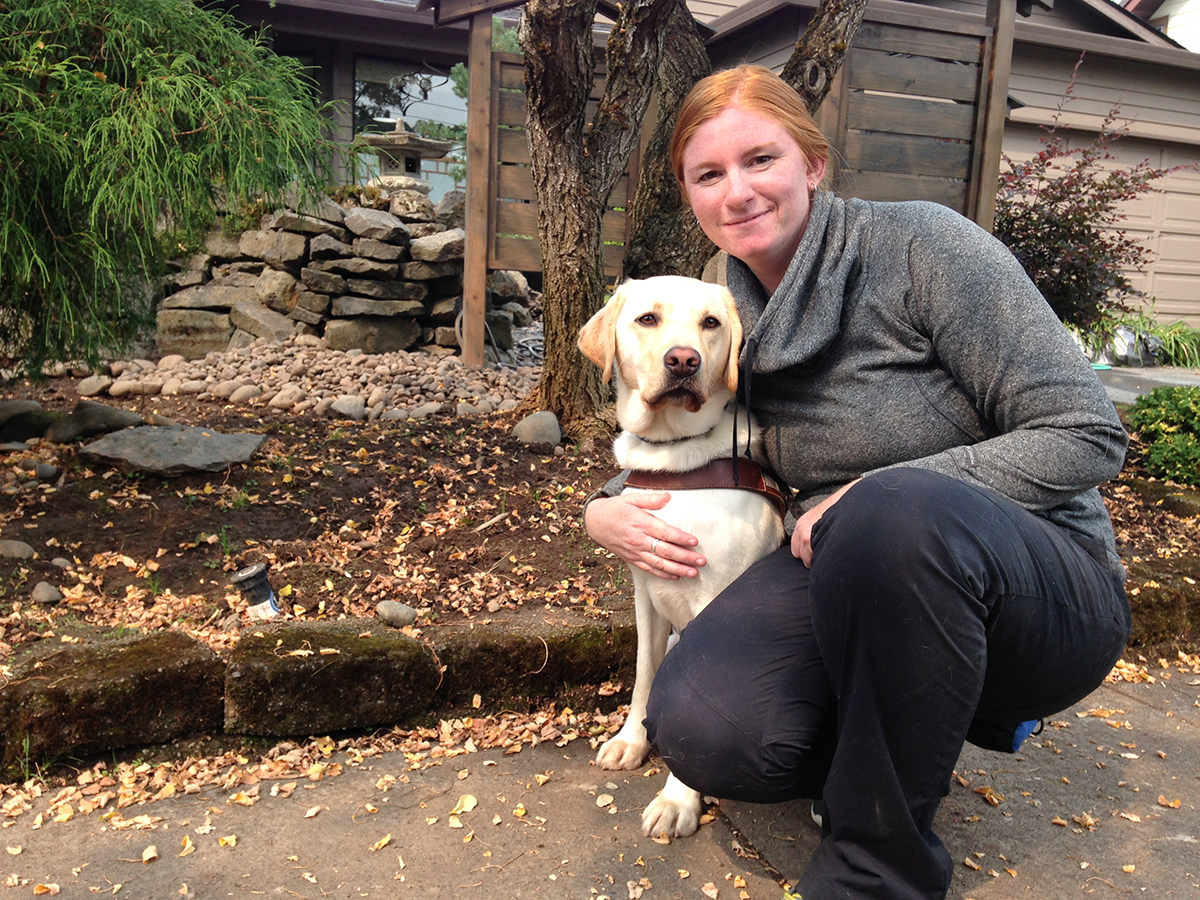 Kaitlin Cherney with a yellow Lab guide dog.