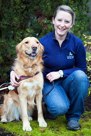 A portrait of Katie Anderson sitting next to a Golden Retriever guide dog.