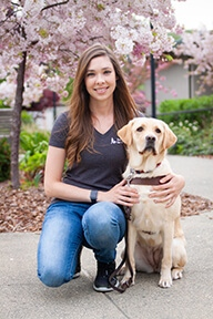 Kerith kneeling next to a yello Lab wearing a harness.  Both are looking into the camera in front of a blooming apple blossom tree.