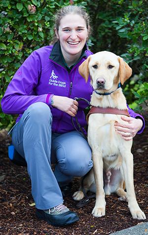 A portrait of LaniJo Bachman sitting next to a yellow Lab guide dog.