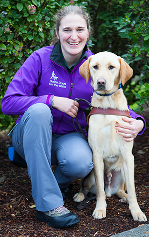 A portrait of LaniJo Bachman sitting next to a yellow Lab guide dog.