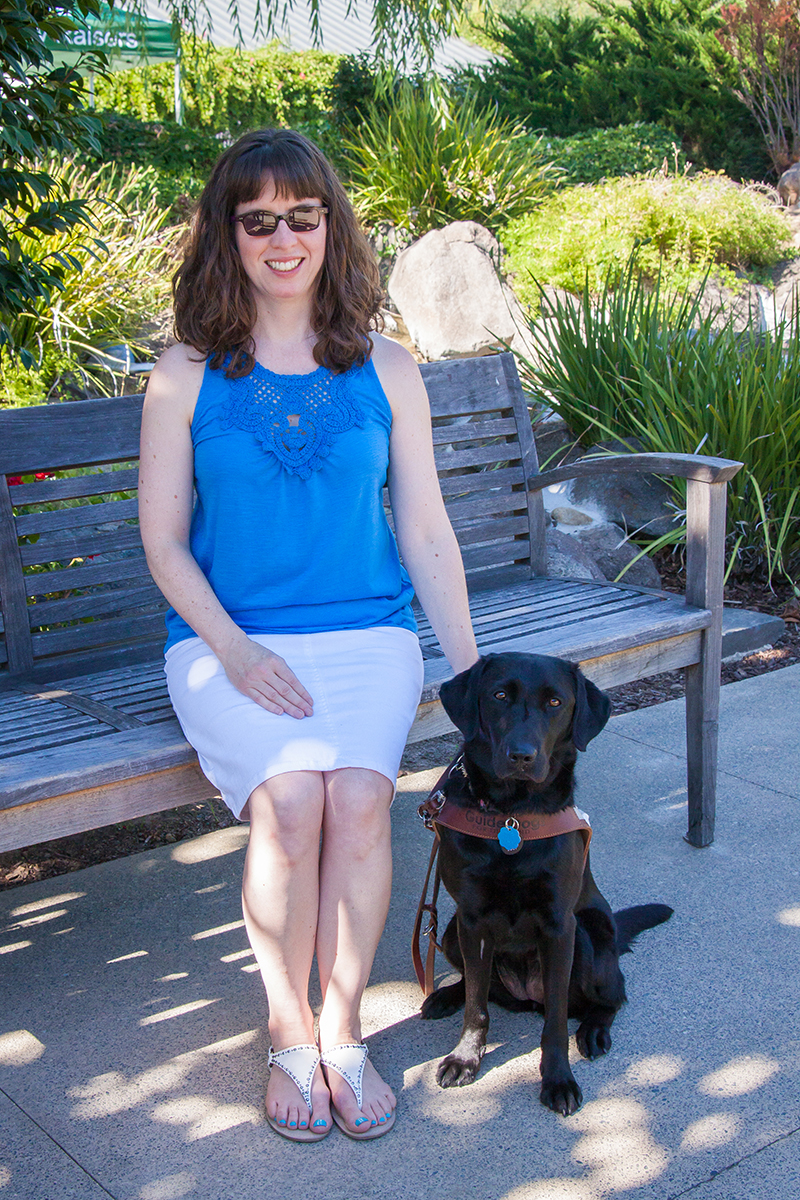 Leanne sits on a bench with her black Lab guide dog Eva.