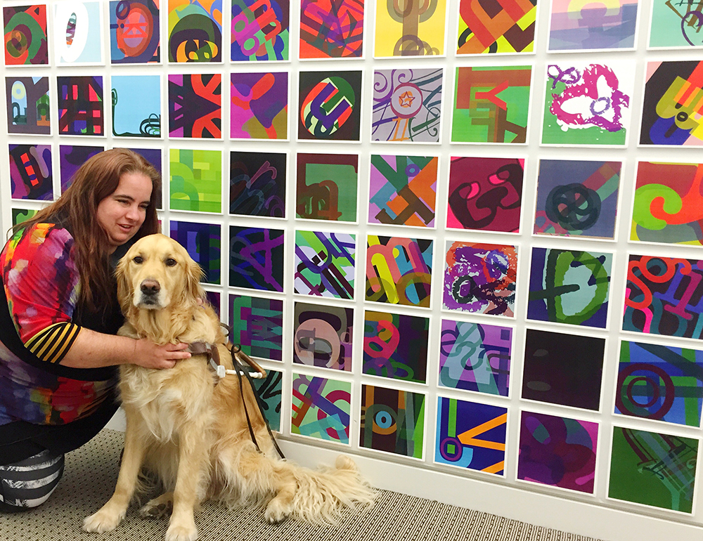Maia Scott and her Golden guide dog, Fiddler, in front of her art installation of colorful tiles.