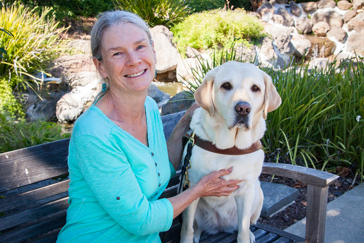 Marcia sits on a bench with her yellow Lab guide dog Viviane.