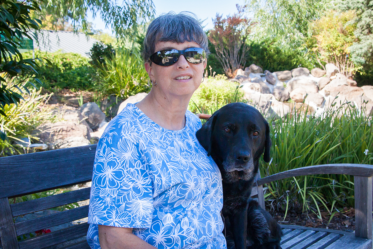 Melanie sits on a bench with her black Lab guide dog Sparta.
