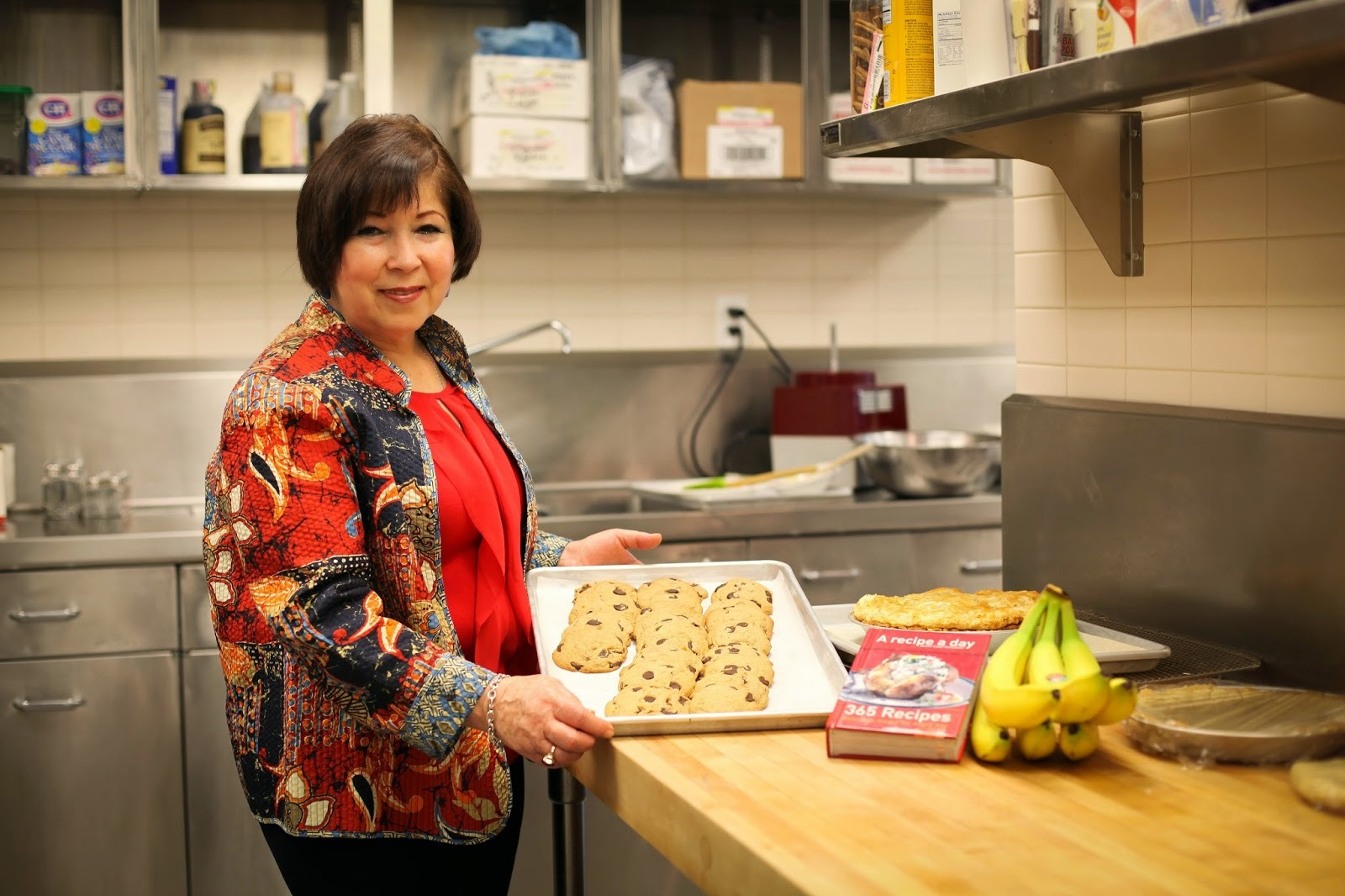 Rose (wearing a beautiful red pattern jacket) poses in the GDB kitchen with freshly baked cookies.