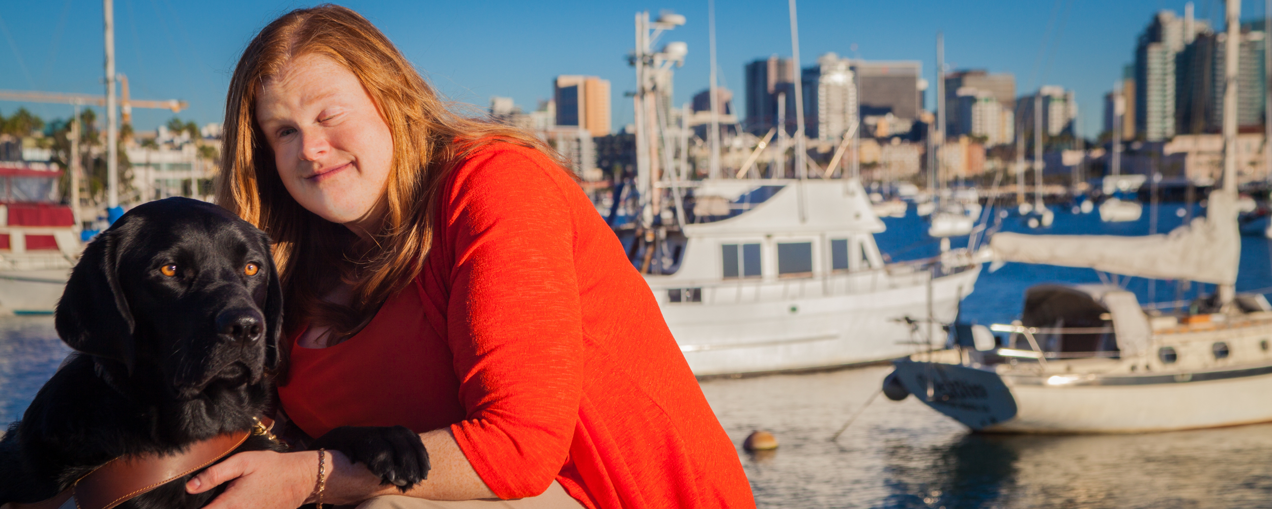A woman wearing a vibrant red top sitting next to her black Lab guide dog in front of a harbor filled with sailboats.
