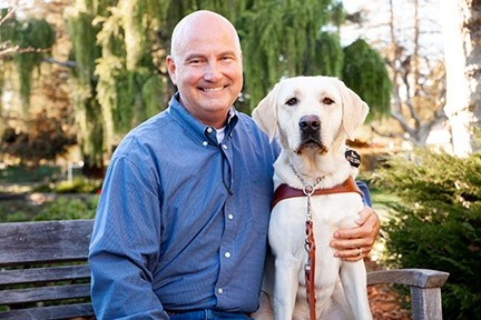 A portrait of Scott Wilcock sitting next to his yellow Lab guide dog, Sailor.