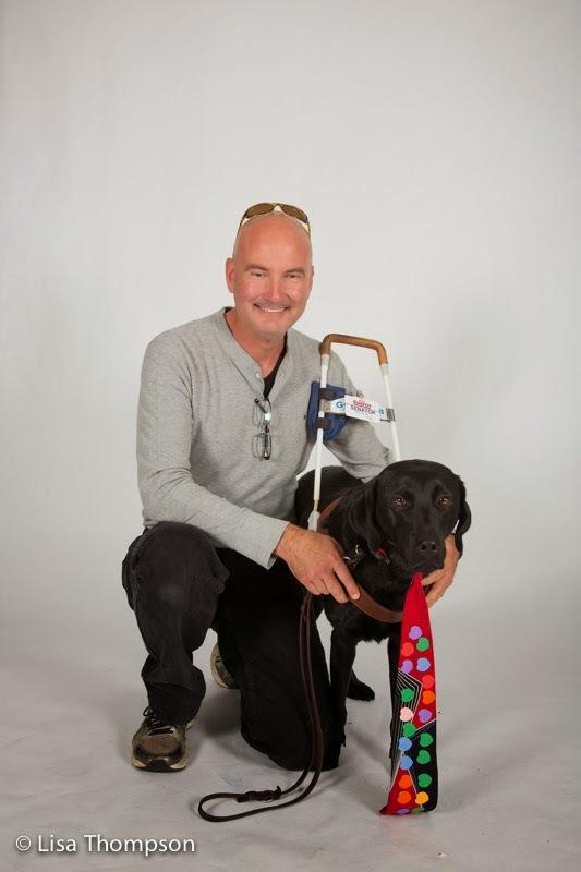 GDB grad Scott Wilcock and guide dog Senator (black Lab) wears a colorful tie.