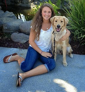 Sophia sits posing with a Golden Retriever in front of the GDB pond
