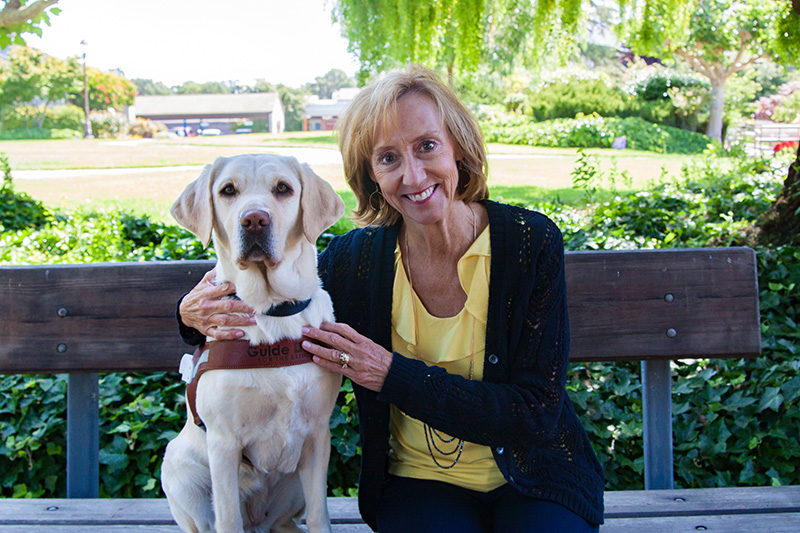 Susan Neff sitting on a bench next to a yellow Lab guide dog.