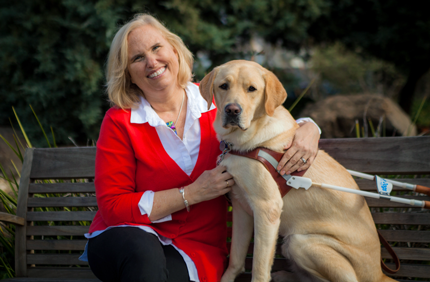 A portrait of Theresa Stern sitting next to her yellow Lab guide dog, Wills.