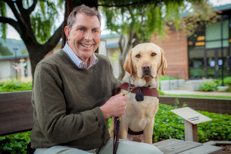 A portrait of Tom Kowalski sitting next to his yellow Lab guide dog, Dynamo..