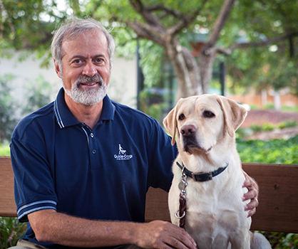 A portrait of Tom Horton sitting next to a yellow Lab.