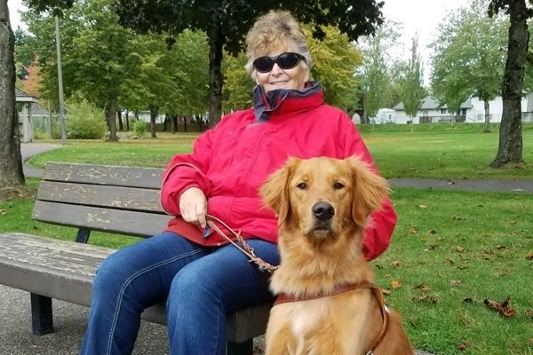 GDB client Sandra Shelby sits next to her Lab/golden cross guide dog Neptune.