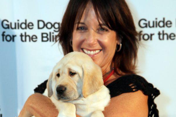 Debi Morgan holding a yellow Lab puppy.