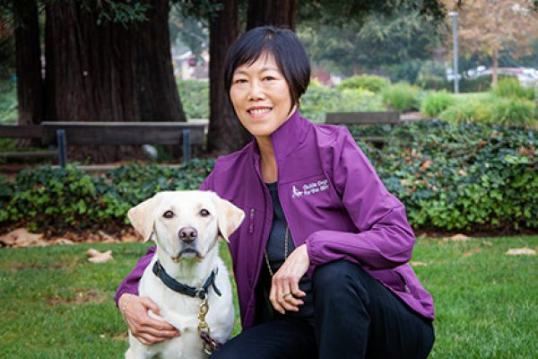 A portrait of Doria Leong with a yellow Lab.