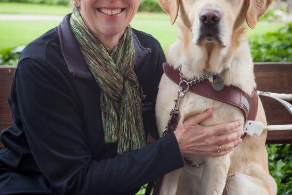 GDB employee Joan Scott sittingon a bench next to a yellow Lab guide dog.