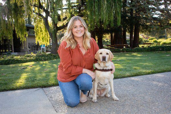 Jillian Fish kneeling next to a yellow Lab guide dog.