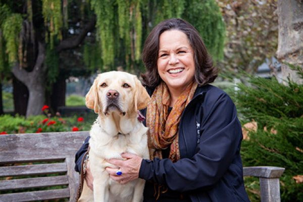 A portrait of Robin Keating with a yellow Lab.