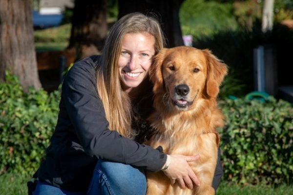 Guide Dog Mobility Instructor Chelsea Sims with a Golden Retriever guide dog.