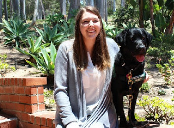 Christina with a black Lab guide dog puppy.