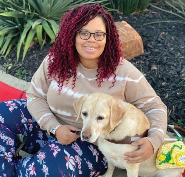 Eryn sitting next to her yellow Lab guide dog, Latke.
