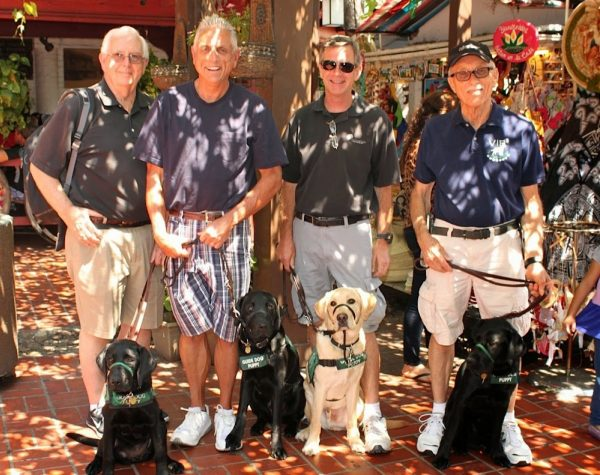 Puppy raisers pose on the sidewalk with their guide dogs puppies (one yellow and three black Lab).