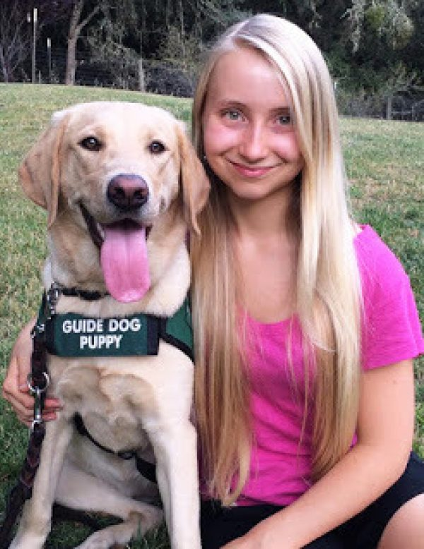 Hailey with a yellow Lab guide dog puppy.