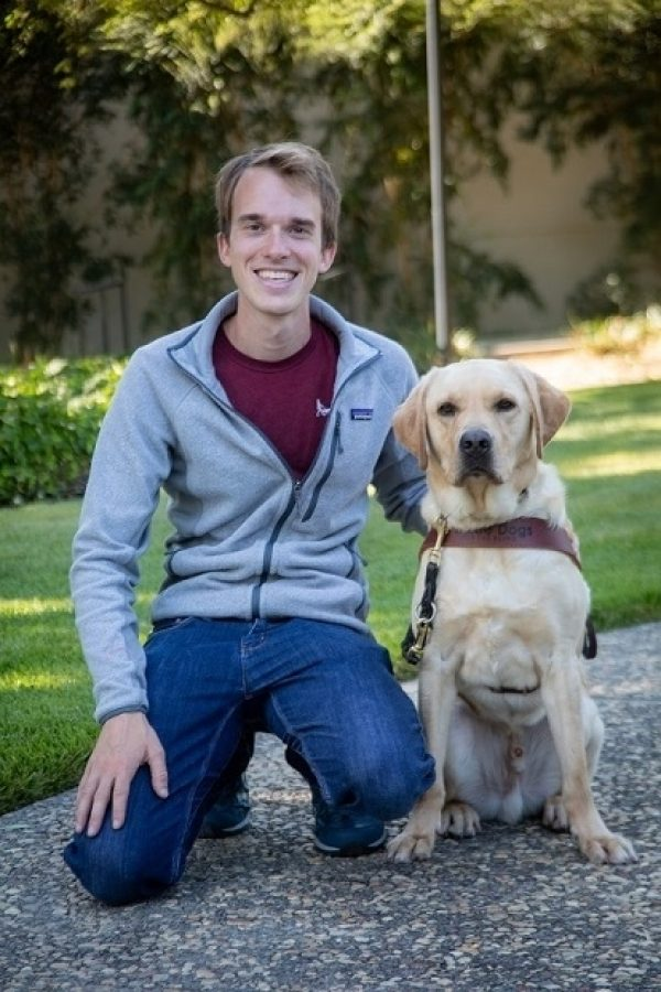 Guide Dog Mobility Instructor, Jack England, kneeling next to yellow Lab guide dog wearing a harness.