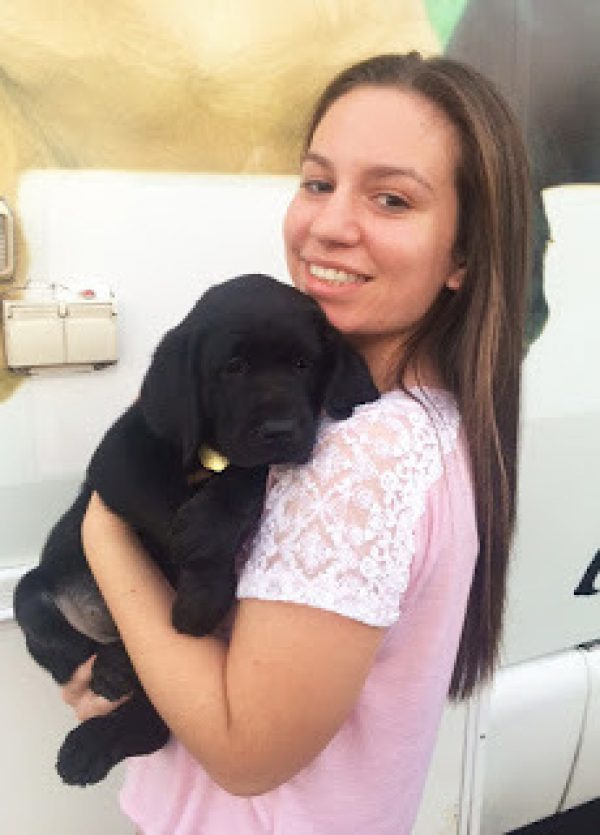 Jaclyn in a pink shirt holding a black Lab puppy.