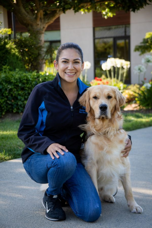 Guide Dog Mobility Instructor Lauren Piperno with a smiling Golden Retriever guide dog by her side.