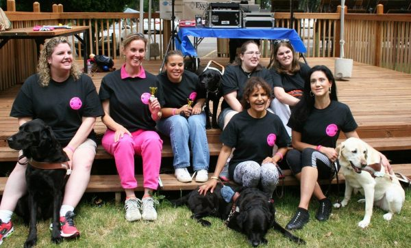 Seven members of Mommies with Guides pose with their black and pink t-shirts and guide dogs