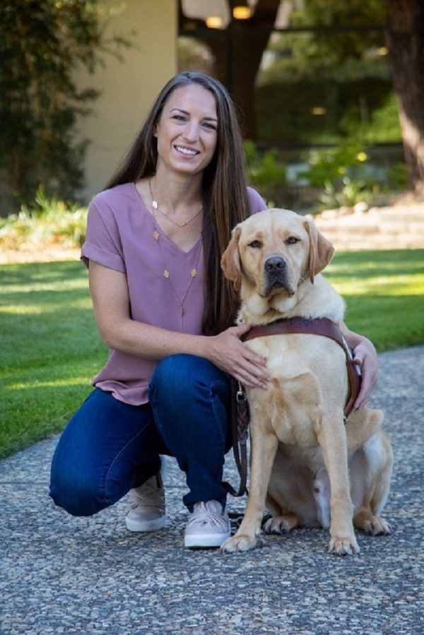 Guide Dog Mobility Instructor Melanie Bell kneeling next to a yellow Lab guide dog by her side.