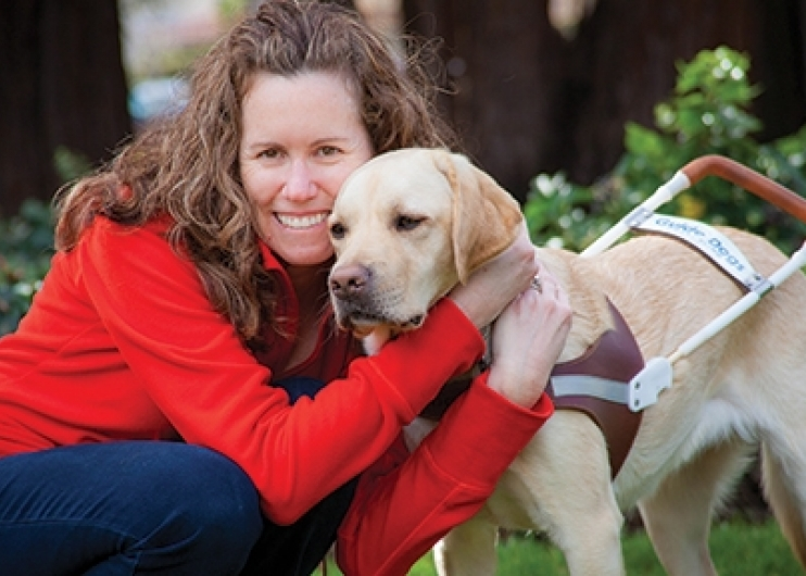A woman hugging her yellow Lab guide dog.