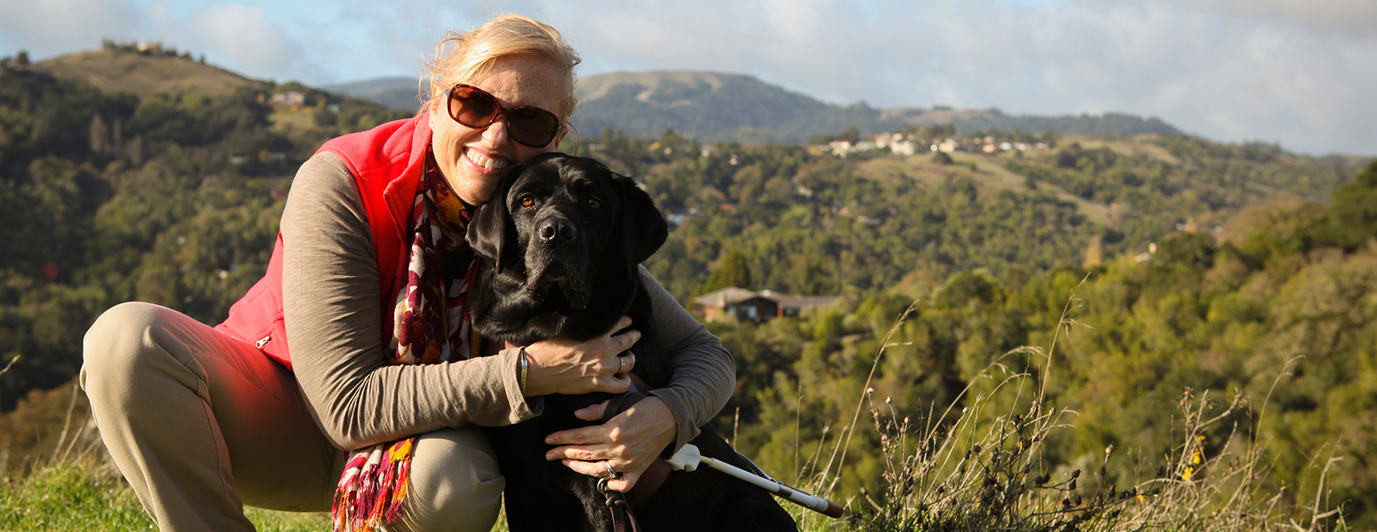 A woman hugging her black Lab guide dog.