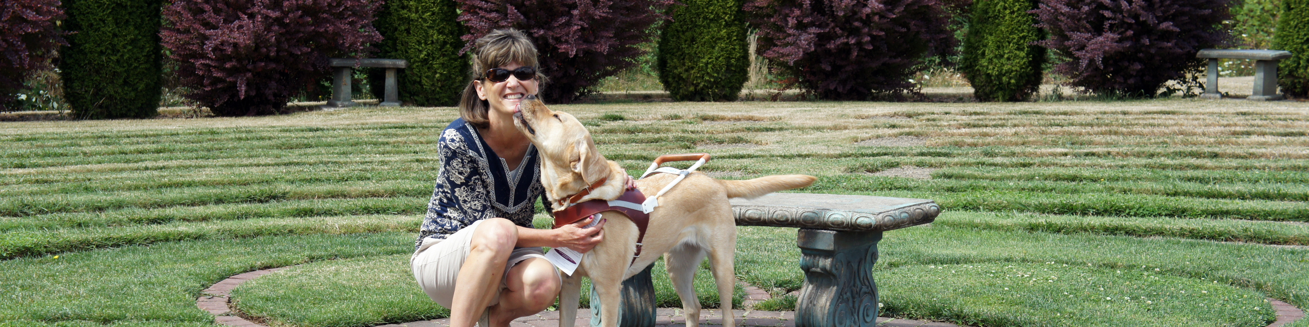 A female GDB graduates kneels down smiling while getting a kiss from her yellow Lab guide dog