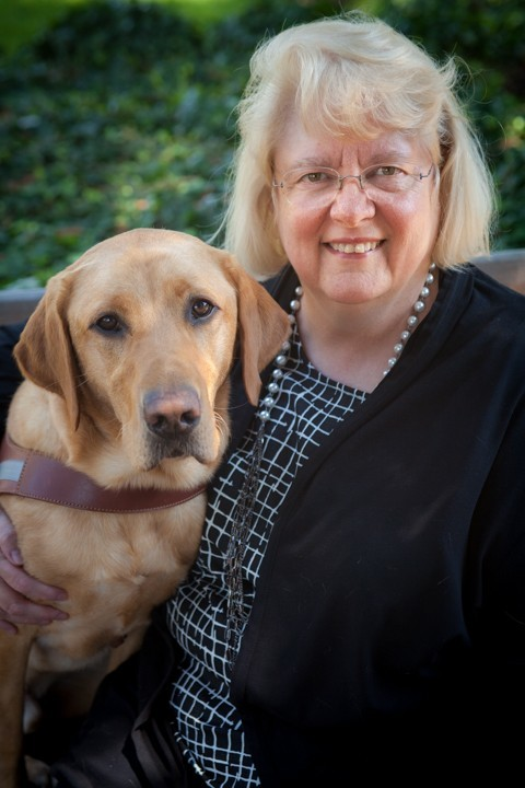 CFO Cathy Martin sitting next to a yellow Lab guide dog.