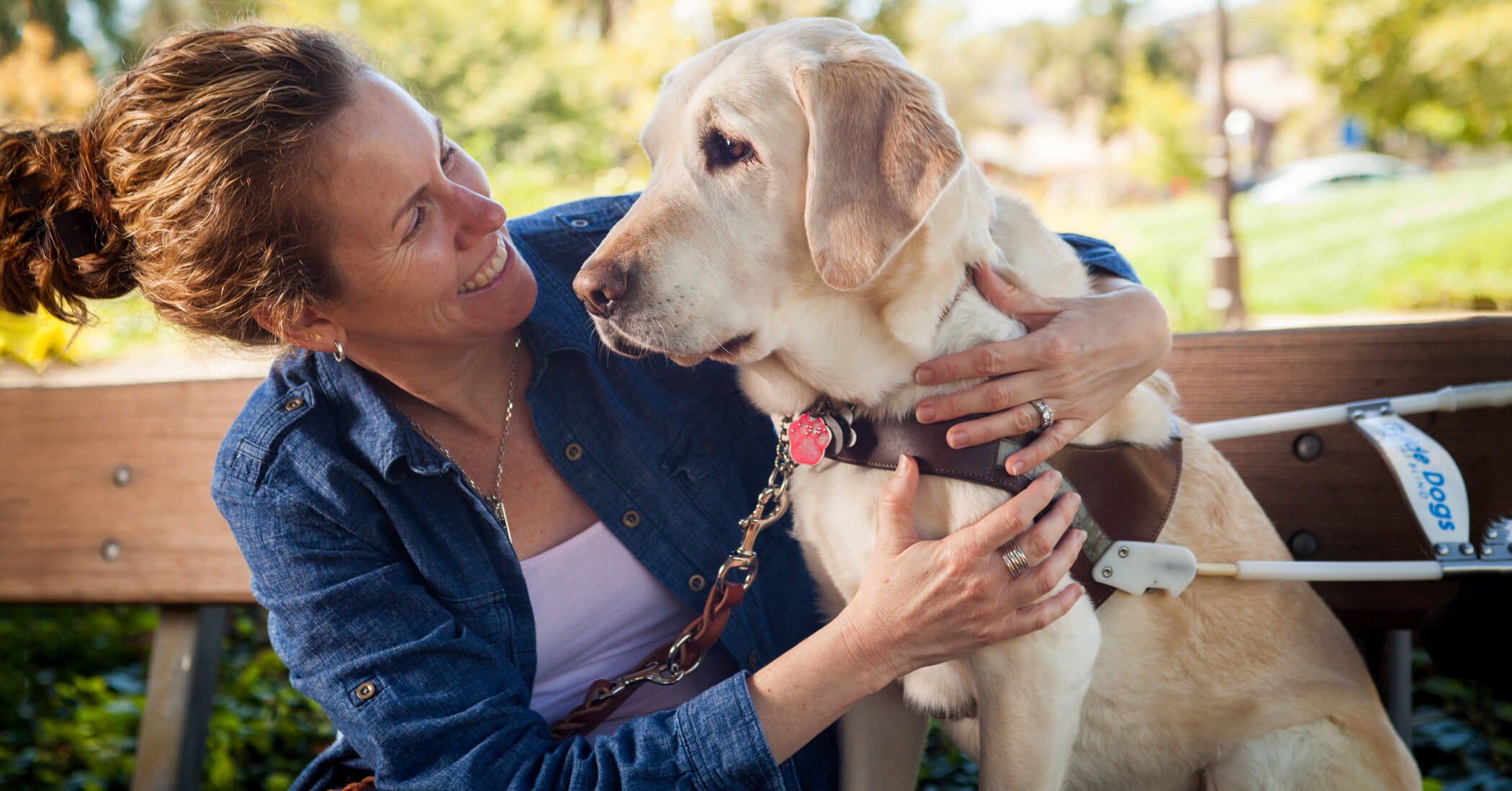 A female GDB graduate smiles with her arms around her guide dog (yellow Lab/Golden Cross)