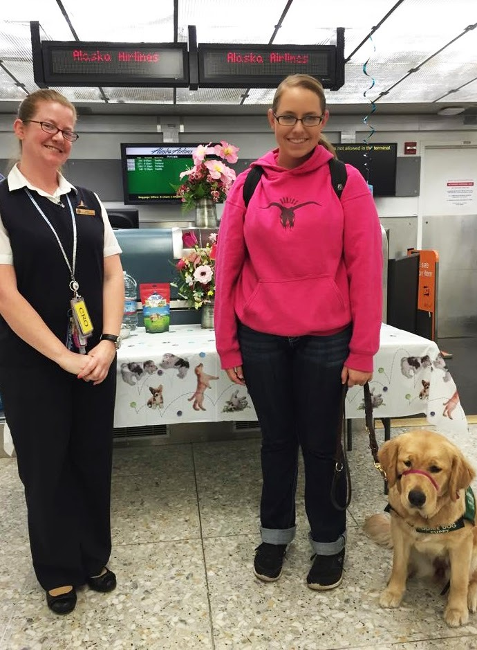 An Alaska Airlines female employee poses with a female puppy raiser with her guide dog puppy in training sitting calmly next to her.
