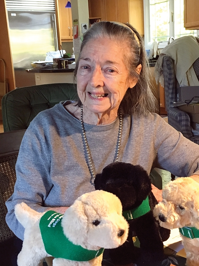 Leslys poses  for a photo surrounded by three plush guide dog puppies wearing green GDB training vests.