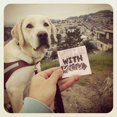"""JR holds up one of his unique typography notes on a post-it that reads """"Who I am with you"""" - his guide dog Griff sits looking at the camera and behind him overlooks San Francisco."""