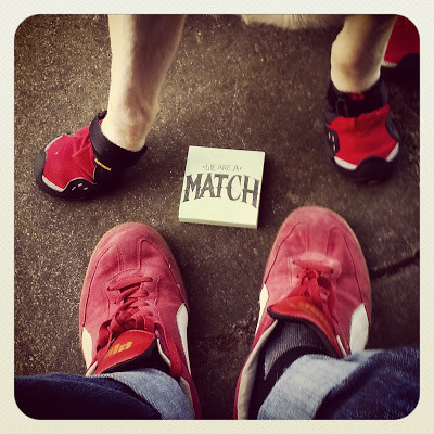 """Shot looking down at JR's red Puma shoes with Griff's red Ruffwear booties and it between them on the pos-it it reads """"We are a match."""""""