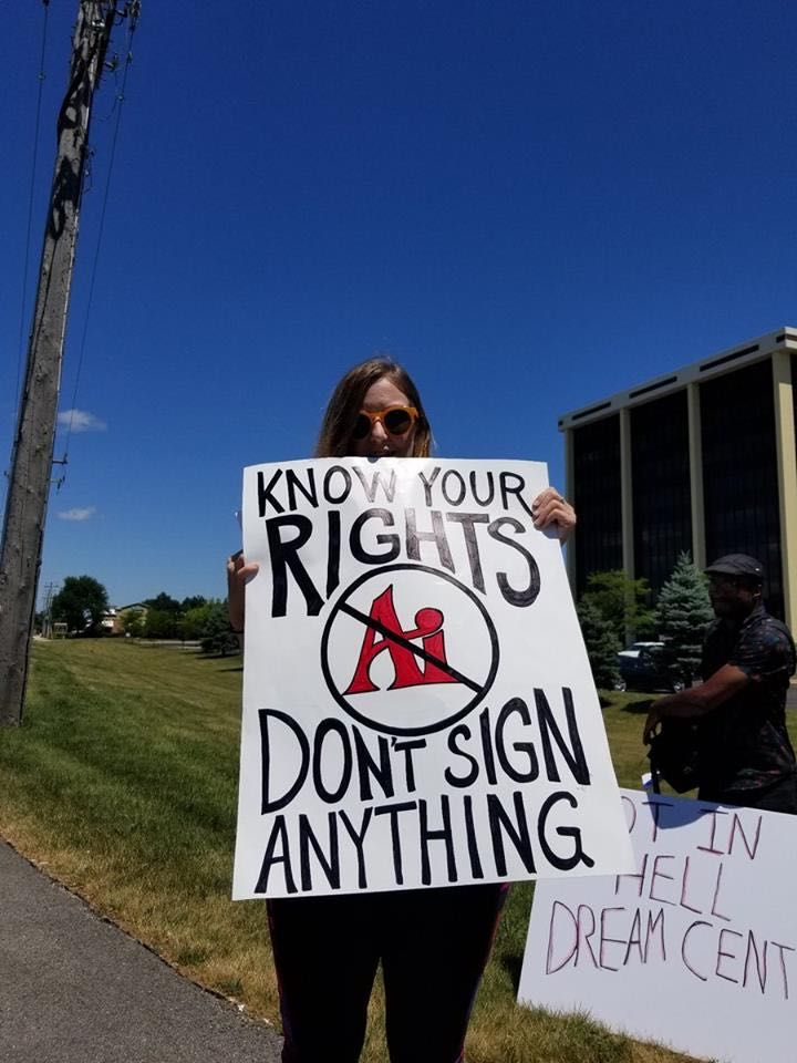 """Ami Schneider holding a """"Know your rights, Don't sign anything"""" protest sign"""