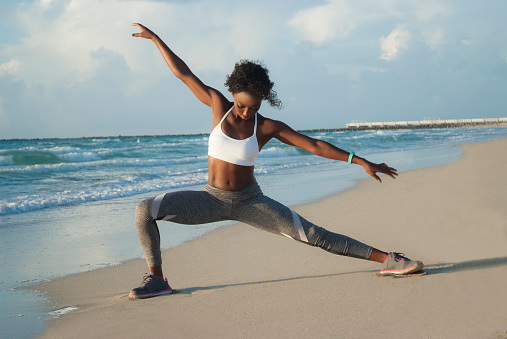 Young woman yoga stretching on beach