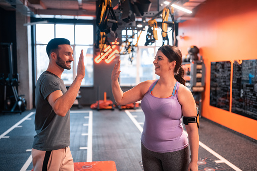 High five. Dark-haired plump excited woman giving high five to her fitness trainer