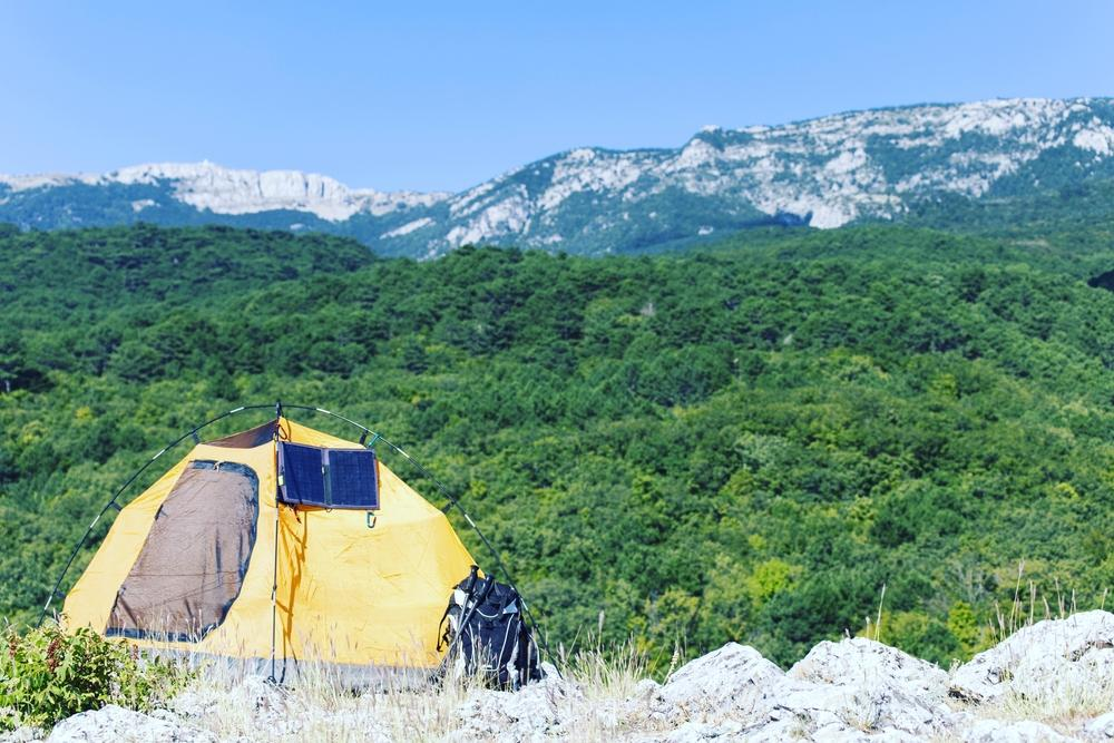 solar powered tent with a backpack and mountain view