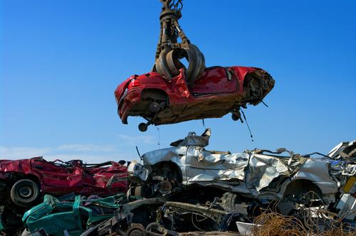 Car lifted by crane in scrapyard
