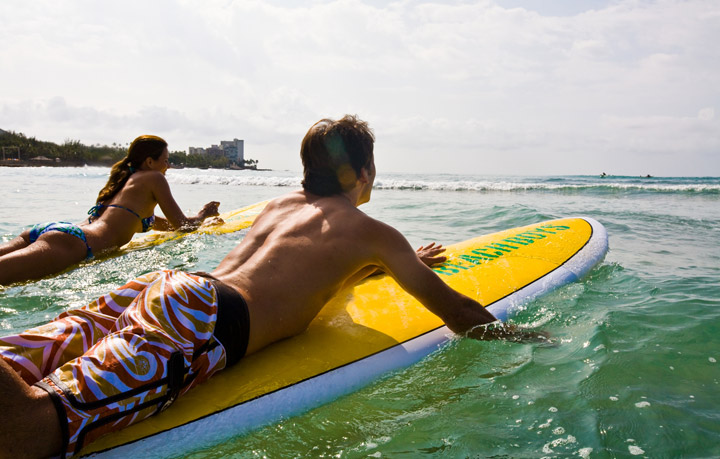 Couple going surfing off Waikiki Beach | Hawaii Tourism Authority (HTA) / Tor Johnson